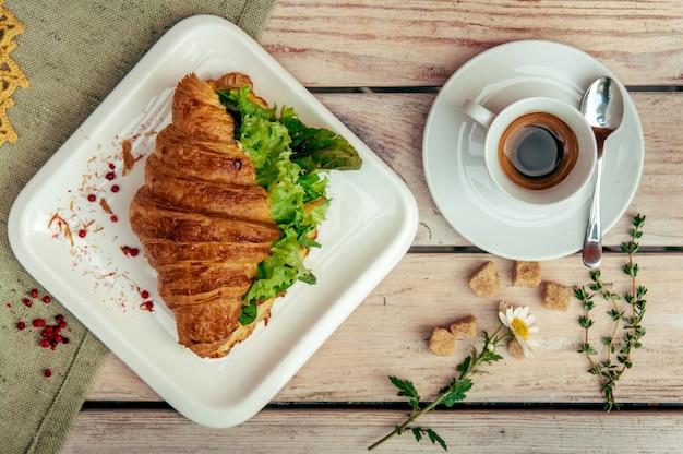 Ontbijt met groene croissant, zwarte koffie versierd met kamille en bruine shugar op houten tafel.