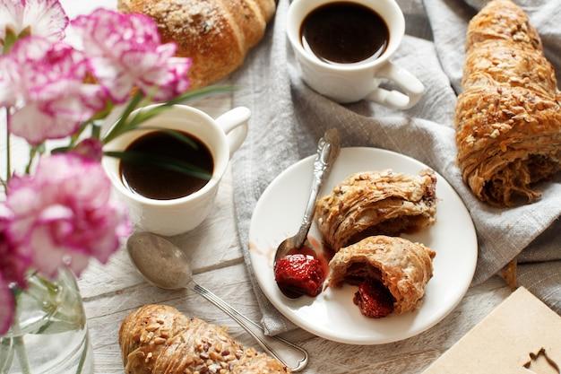 Ontbijt met koffie en croissant met aardbeienjam close-up