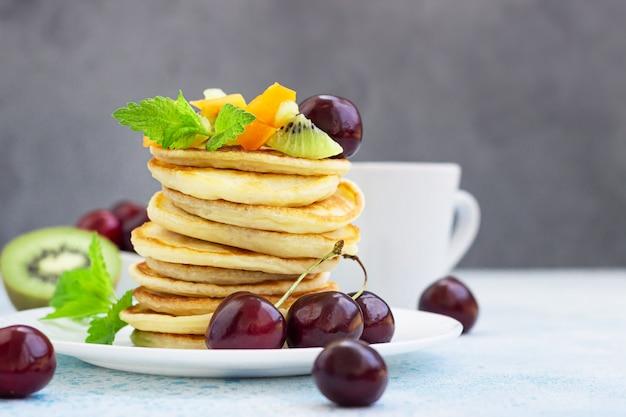 Ontbijt met koffie en een stapel pannenkoeken geserveerd met zwarte kers, abrikoos, kiwi en munt
