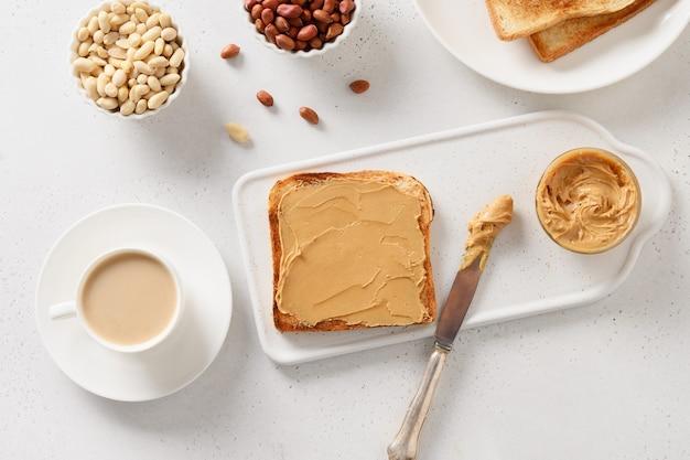 Ontbijt met koffie en knapperige toast met pindapasta.