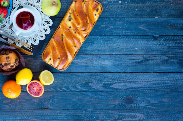 Ontbijt met koffie en thee met verschillende gebakjes en fruit op een houten tafel