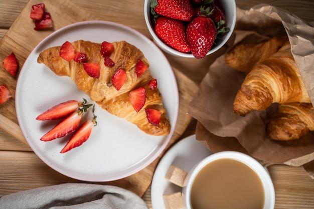 Ontbijt met koffiekopje, croissants, room en verse bessen.