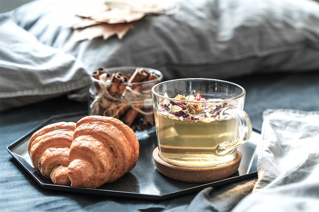 Ontbijt met kruidenthee en croissants op het bed met grijze lakens in een zonnige kamer