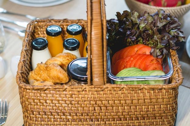 Ontbijt met melk, sinaasappelsap, stokbrood of stokbrood met komkommertomaat op de eettafel