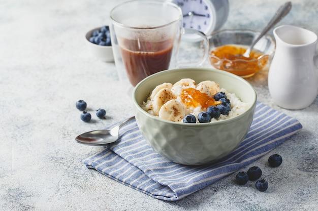 Ontbijt met melkrijstepap met bananen, bosbessen en sinaasappeljam, romige rijstpudding of franse riz au lait in een kom, glazen beker met cacao en wekker