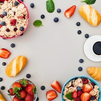 Ontbijt met muesli, fruit, bessen, noten op grijze achtergrond.