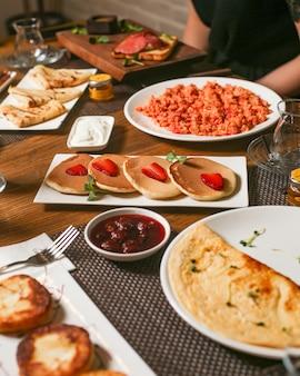 Ontbijt met pannenkoeken pannenkoeken jam omelet en eieren met tomaten