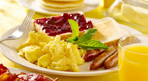 Ontbijt met roerei, worstjes en toast