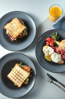 Ontbijt met sandwiches op borden, benedictus-eieren met tomaten en ham met bestek en vers sinaasappelsap