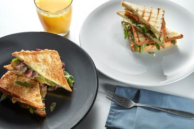 Ontbijt met sandwiches op borden en ham met bestek en vers sinaasappelsap