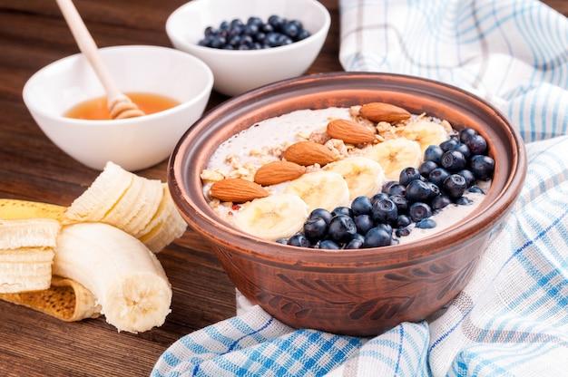 Ontbijt met smoothiekom met banaan, bosbessen, amandel en honing