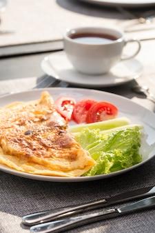 Ontbijt met thee en gebakken eieren met tomaten en komkommers en thee