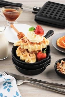 Ontbijt met vers gebakken heerlijke zelfgemaakte croissantwafel met ahornsiroop, gehakte amandel en aardbei. geserveerd op mini gietijzer met melk