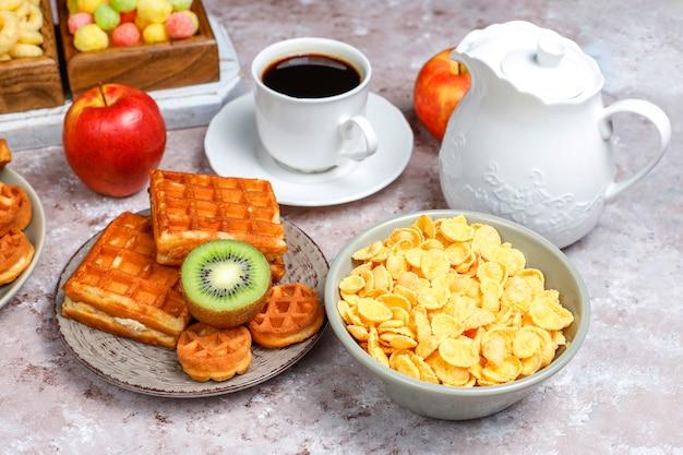 Ontbijt met verschillende snoepjes, wafels, cornflakes en een kopje koffie, bovenaanzicht
