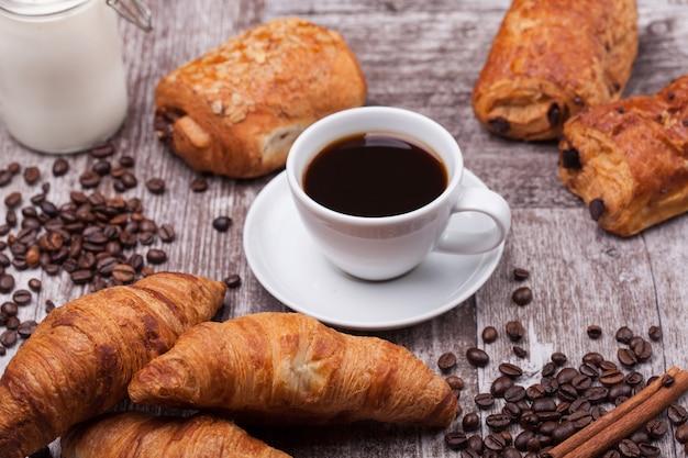 Ontbijt met verse coissants met koffie en melk op rustieke houten tafel. gouden croissant.