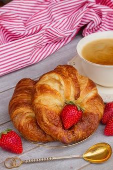 Ontbijt met verse croissants en aardbeien op tafel