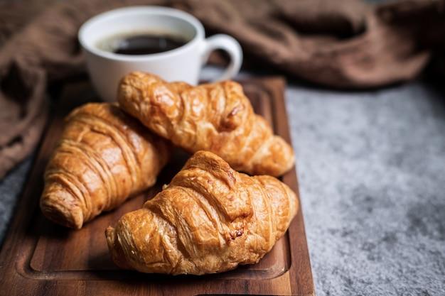 Ontbijt met verse croissants en kopje zwarte koffie op een houten bord