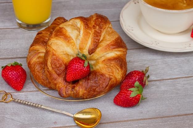 Ontbijt met verse croissants en verse aardbeien op tafel