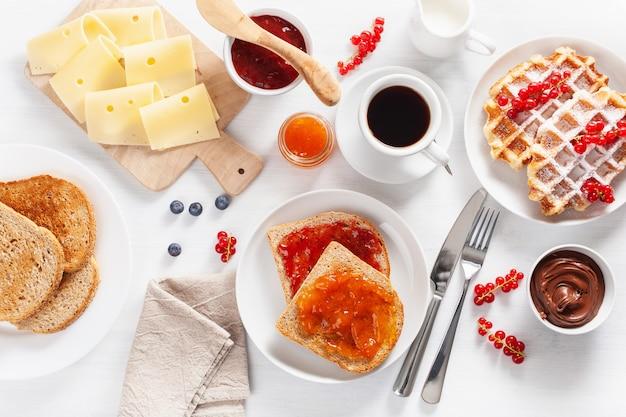 Ontbijt met wafel, toast, bessen, jam, chocopasta en koffie. bovenaanzicht