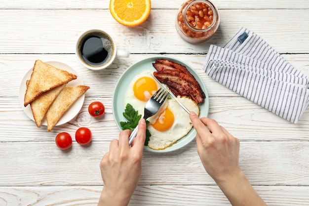 Ontbijt of lunch met gebakken eieren op houten tafel, bovenaanzicht. vrouw eet