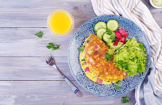 Ontbijt. omelet met radijs, rode ui en verse salade op blauwe plaat. frittata - italiaanse omelet. bovenaanzicht