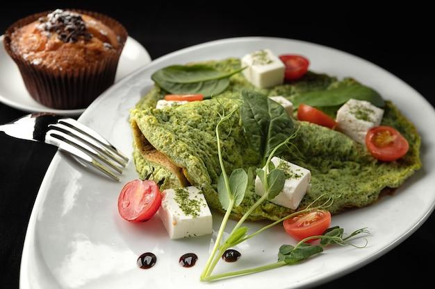 Ontbijt. omelet met spinazie en kaas op een witte plaat, op een zwarte ondergrond