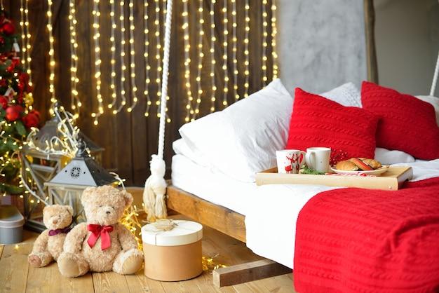 Ontbijt op bed, dienblad met kop koffie en croissant. modern slaapkamerinterieur. romantische ochtendverrassing.
