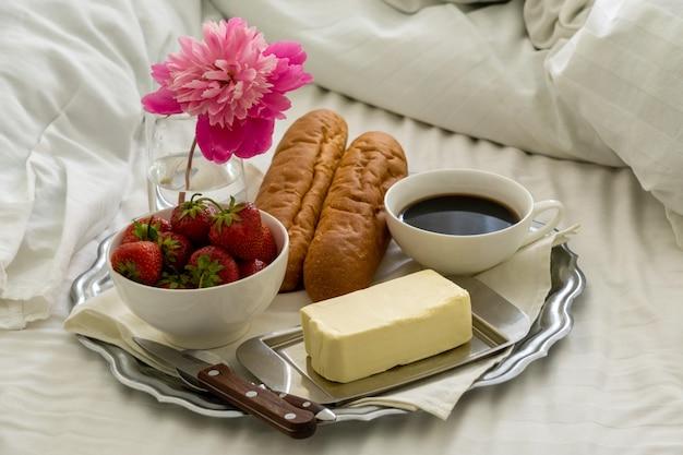 Ontbijt op bed. dienblad met zwarte koffie, stokbrood en aardbeien