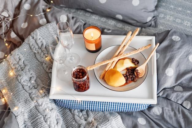Ontbijt op bed, een dienblad met kaas, grissini, jam van jonge dennenappels, champagne en een kaars