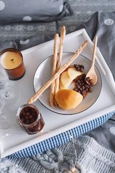 Ontbijt op bed, een dienblad met kaas, grissini, jam van jonge dennenappels en een kaars