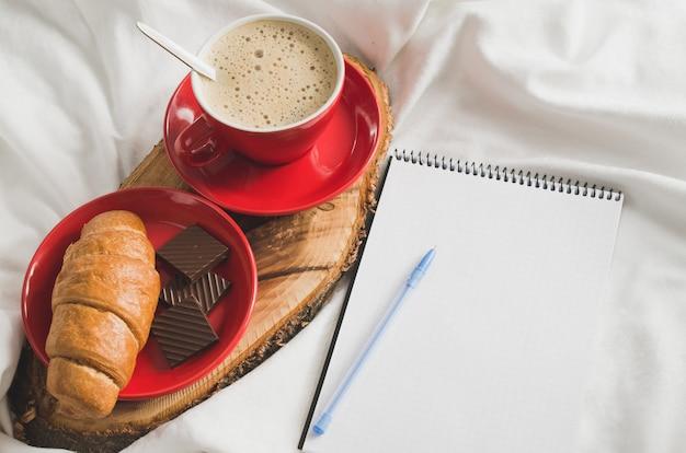 Ontbijt op bed en lege laptop voor notities.