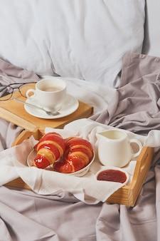 Ontbijt op bed, koffie met slagroom, croissants in jam