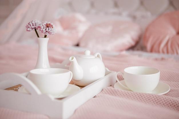 Ontbijt op bed met bloemen en witte kopjes.