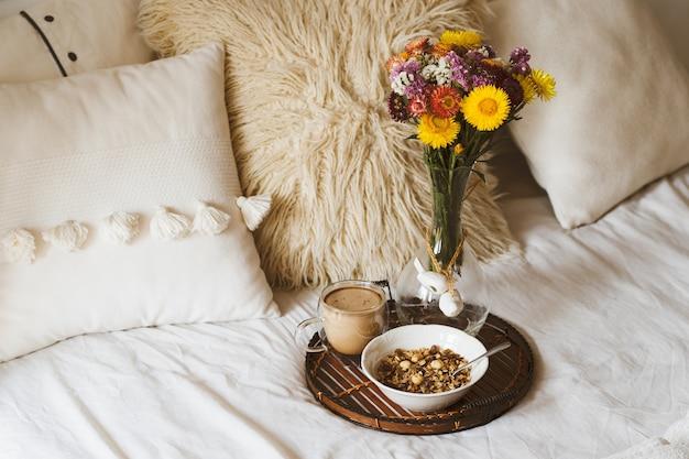 Ontbijt op bed met boeket bloemen