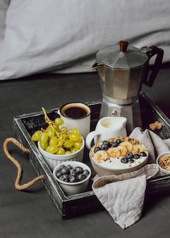 Ontbijt op bed met bosbessen en ontbijtgranen op dienblad
