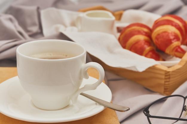 Ontbijt op bed met espresso, bloem en croissant