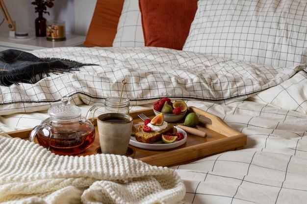 Ontbijt op bed met gebak en vers fruit, zwarte thee
