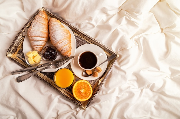 Ontbijt op bed met koffie en croissants