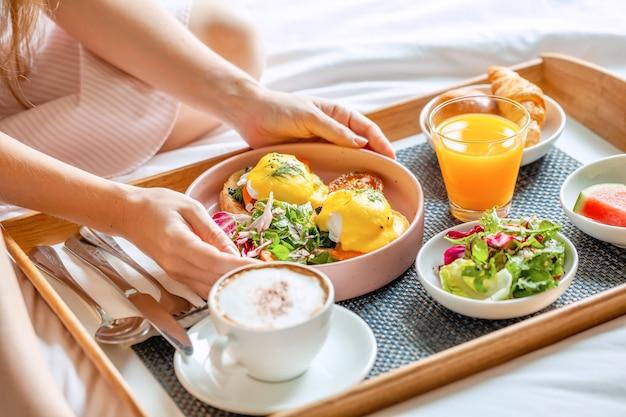 Ontbijt op bed met koffie, sinaasappelsap, salade, fruit en eggs benedict