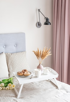 Ontbijt op bed met kop met cappuccino, donuts en witte tulpen