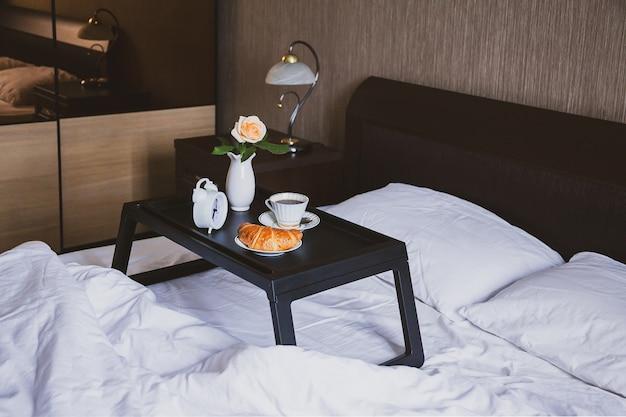 Ontbijt op bed op een dienbladtafel met roos in een vaas