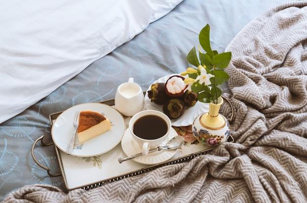 Ontbijt op bed plak van kaastaart en fruit met kop van koffie en bloem in een dienblad.