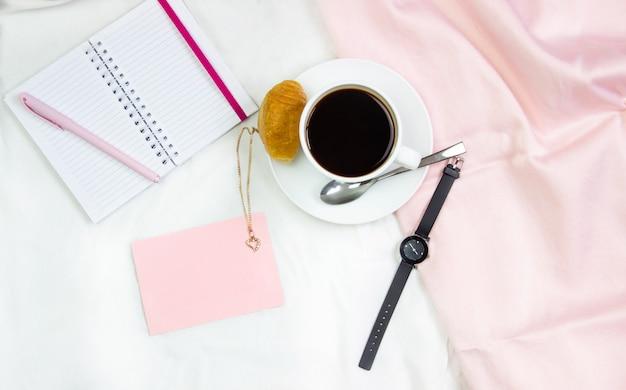 Ontbijt op bed. platte compositie met koffie, croissants en een notitieblok om te schrijven. lifestyle frame. bovenaanzicht op vellen