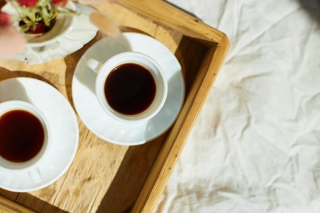 Ontbijt op bed, probeer met twee kopjes koffie en bloem in het zonlicht thuis, kamermeisje brengt dienblad met ontbijt in hotelkamer, goede service