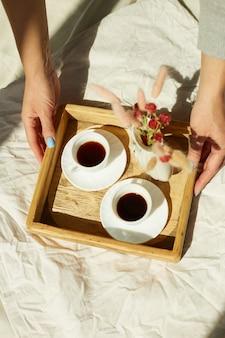 Ontbijt op bed, vrouwelijke handen zetten proberen met twee kopjes koffie en bloem in zonlicht thuis, kamermeisje brengt dienblad met ontbijt in hotelkamer, goede service