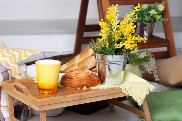 Ontbijt op de gezellige veranda. zelfgemaakte limonade op de veranda op een warme dag. zomer buitenplaats met kussens, mimosa bloemen en limonade. mooie zomeravond op houten terras of patio.