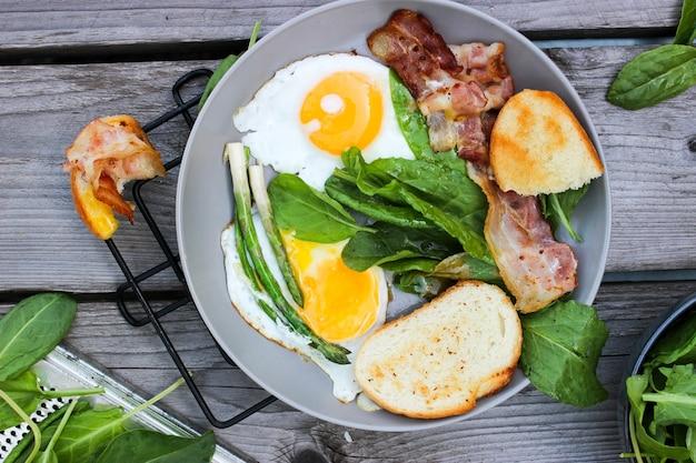 Ontbijt op een bord roerei met geroosterd brood, spek en aromatische kruiden