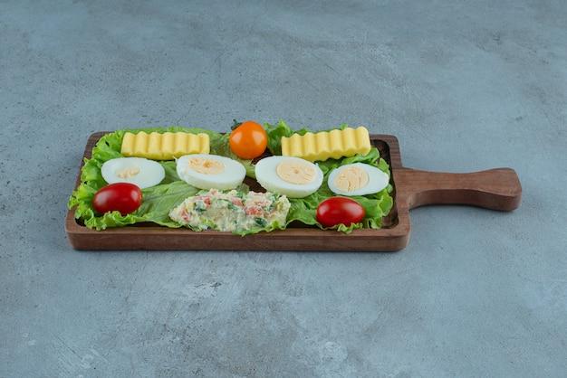 Ontbijt op een houten dienblad met groenten, gekookte eieren, boter en een salade serveren, op marmeren achtergrond. hoge kwaliteit foto