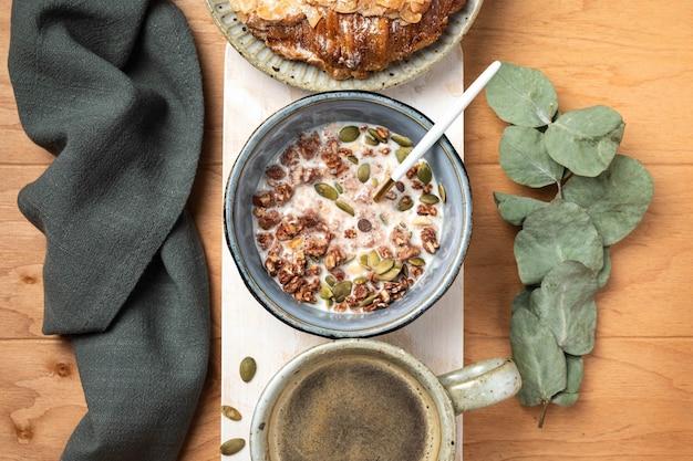 Ontbijt op een houten tafel: muesli, croissant en koffie, bovenaanzicht