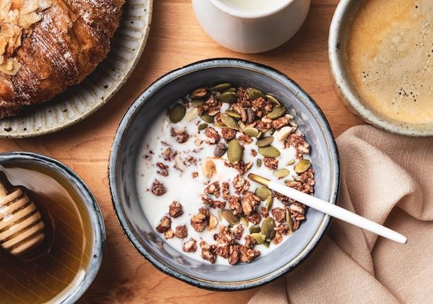 Ontbijt op een houten tafel: muesli, croissant, koffie en melk,